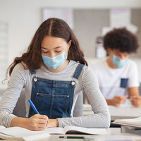 Two high school students are wearing masks while reading books at their desks.