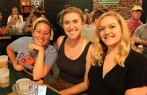 Three college girls smiling while at Shakespeare's Downtown for Trivia Night
