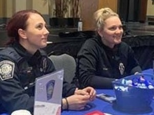 Officers smiling at their table at the Safety Fair