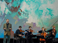 A man in a suit jacket, gesturing with open hands as he speaks, next to a seated string quartet playing their instruments. In the background, a large colorful projection of a painting that evokes a satellite map