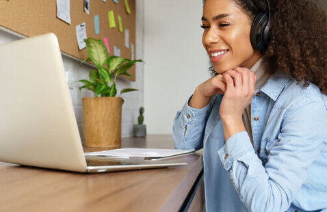 Image of a woman on her laptop with headphones on