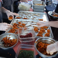 Assembly line of people prepare food