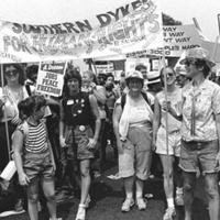 """Black and white photo of women marching in protest with banner that reads """"Southern Dykes for Human Rights"""""""