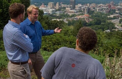 Two students and professor look out over downtown Asheville from a high vantage point.