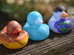 Decorated rubber ducks sitting on bridge railing