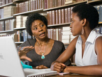 Two women talking at table with computer - bookshelf in background