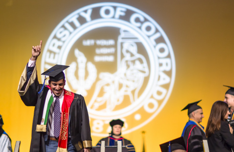 graduate crossing ceremony stage. University of Colorado seal in background.