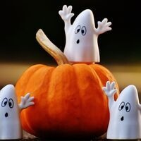 This image has a pumpkin on it and it is surrounded by 3 ghosts with their hands up.