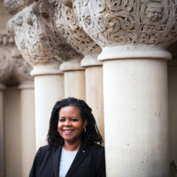 Annette Gordon-Reed stands against a column outside the Harvard Law Building. She wears a black suit jacket and white blouse and is smiling at the camera.