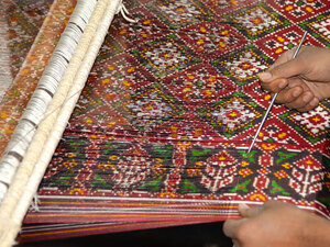 graphic of woman weaving a colorful tapestry