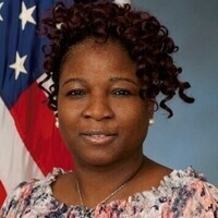 Dr. Frederica Free-Nelson with American flag behind her.