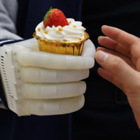 Inflatable robot hand passing a cupcake to a human hand