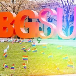 BGSU letters in the oval with various LGBTQ+ pride flags in the foreground
