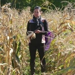 Angela standing in a cornfield holding an ear of corn.