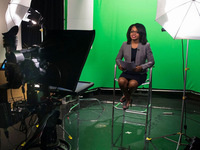 communications student in front of green screen