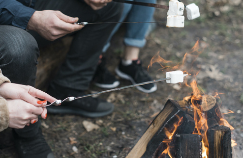 Marshmallows are held out over a bonfire.