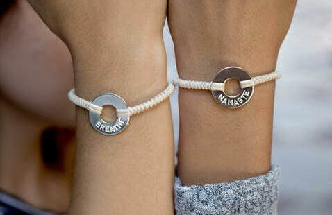 Two people hold up their wrists to show handmade bracelets.