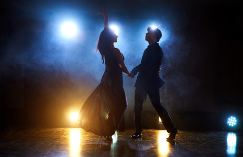 Two dancers perform on a darkly lit stage.
