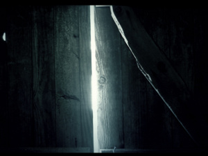 eerie photo of two old doors opening inward and light shining between them