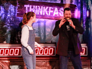 A student and game show host participating in a game.