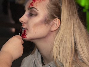 A student having Halloween makeup applied to her face.