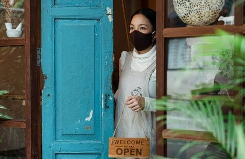 Person stands at open door holding an open sign and wearing a mask