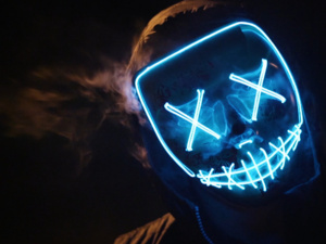 photo of cloaked figure with a blue neon mask with XX for eyes and a stitched mouth