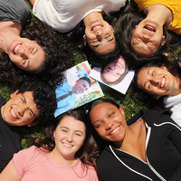 A group of students laying on grass, smiling at the camera.