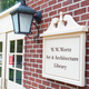 Library sign on the red brick Alumni Hall Building