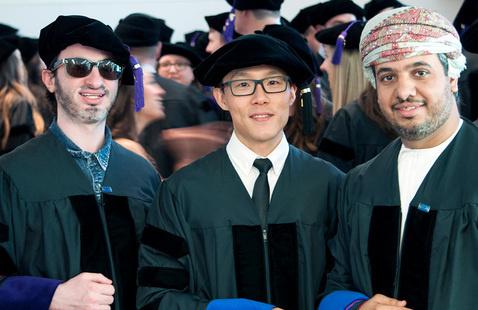 Three international students in regalia at law school graduation