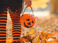 child at halloween with candy bucket in Fall leaves