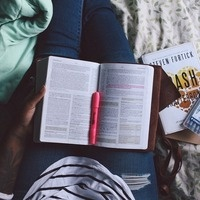 black woman reads a book and takes notes