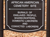Black sign with white text designating the African American Cemetery Site