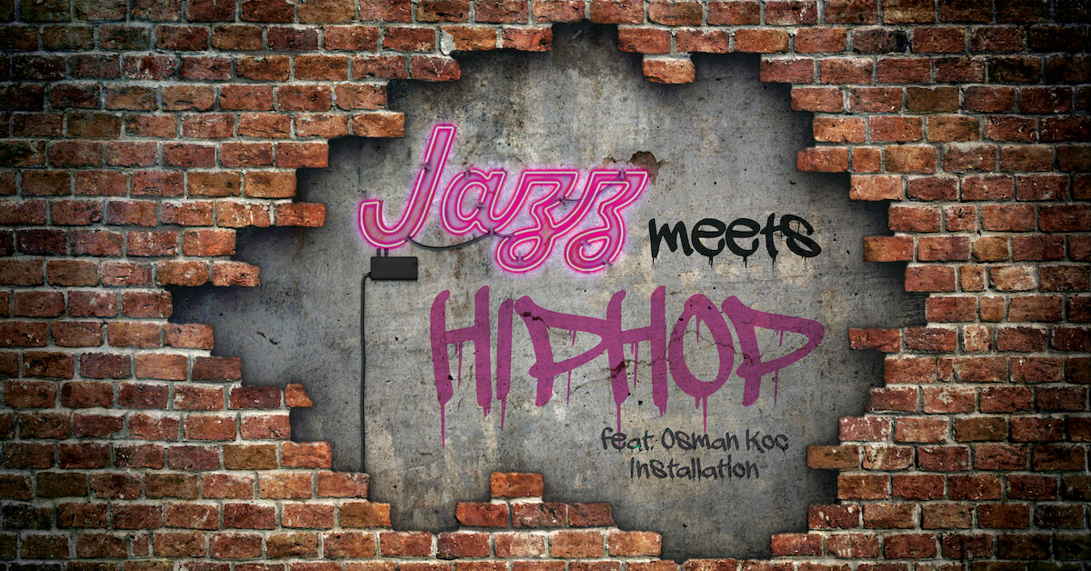 """A Brick wall that has been broken through to reveal a concrete wall with the words """"Jazz Meets Hiphop Feat. Osman Koç Installation"""""""