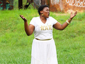 Singer Jacquea Mae standing in a field in a white skirt and white shirt.