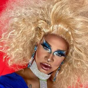 Photo of Gizelle DeVaux, a Black drag queen with large blond hair, blue makeup and top, and silver/blue jewelry.