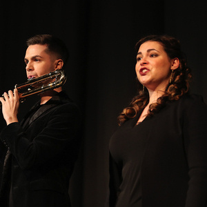 A musician playing a flute and a musician singing