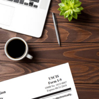 Form I-9 on a wooden desk next to a pen and cup of coffee