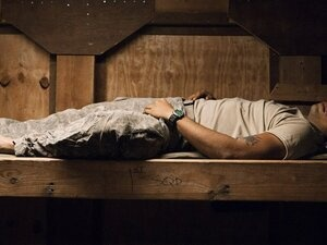 a soldier asleep on a wooden bed without a mattress